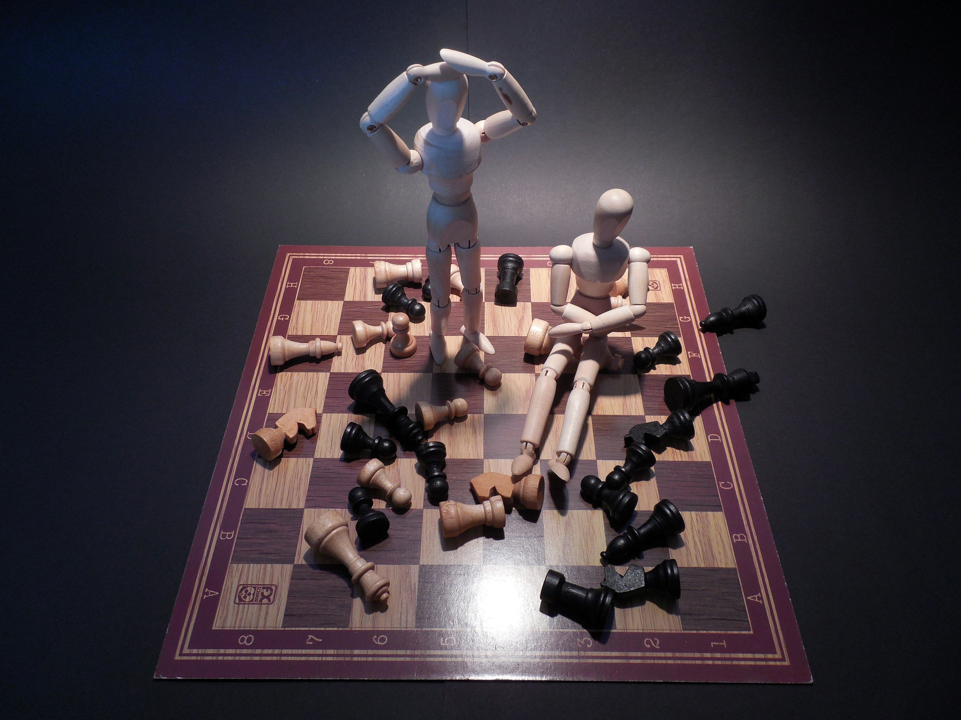 Wooden figures on a checkerboard miming symptoms of chronic stress