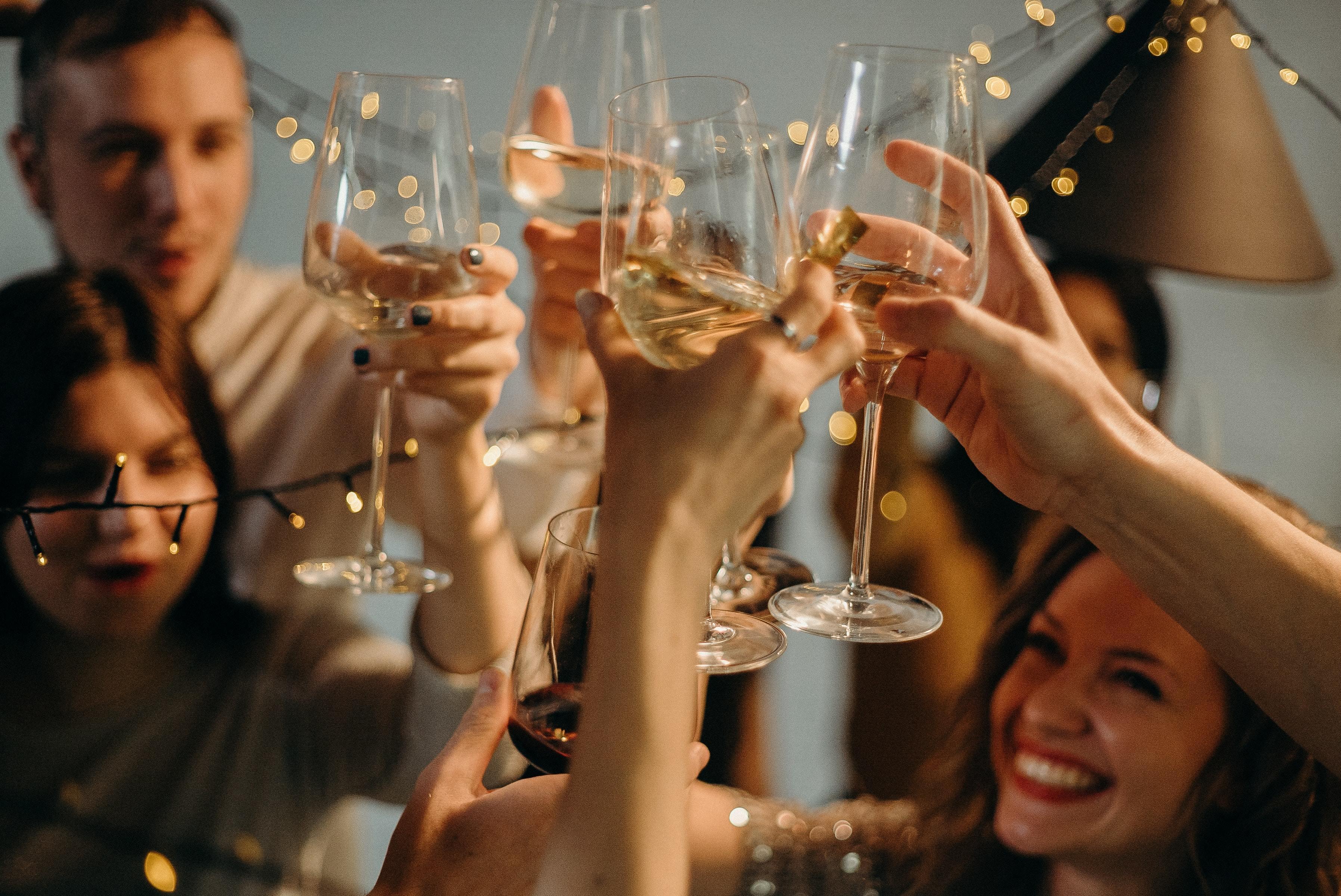 Eine Gruppe von Freunden feiert an einem Low Carb Cheat Day mit trockenem Wein