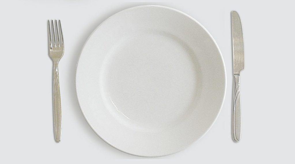 An empty white plate symbolizes that fasting can boost your immune system to fight the coronavirus