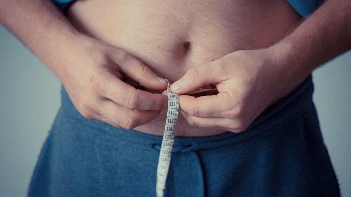 Ein Mann misst seinen Bauchumfang und fragt sich, warum Stress Bauchfett und Gewichtszunahme verursacht