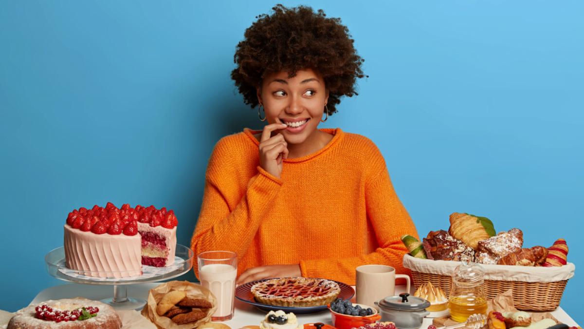 Eine Frau sitzt vor einem verführerischen kohlehydratreichen Cheat Meal und fragt sich, wie oft man bei der Keto Diät einen Low Carb Cheat Day haben kann