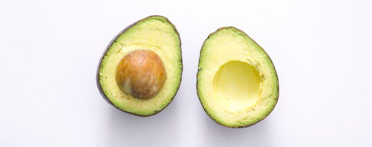 Diese in Hälften geschnittene Avocado ist ein Lebensmittel mit gesunden Fetten, um schneller fett-adaptiert zu werden und nach dem Low Carb Cheat Day in Ketose zu gelangen