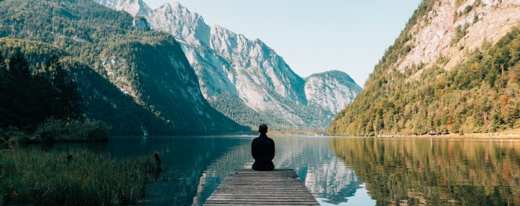 A man sitting and meditating in front of a quiet lake to reduce chronic stress and lose weight
