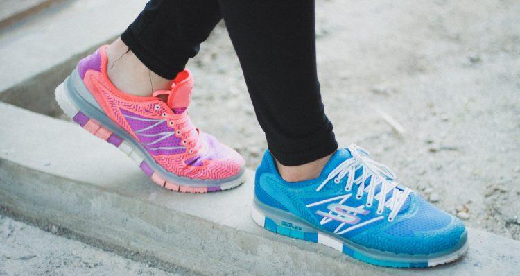 Eine Frau, die in rosa und blauen Schuhen trainiert, um die Insulin- und Cortisolspiegel zu senken und abzunehmen, da Stress aufgrund der Beziehung zwischen Insulin und Cortisol zu Gewichtszunahme führen kann