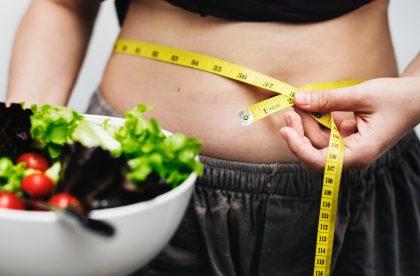 Eine Frau misst ihren Taillenumfang, um festzustellen, ob Stress Fett am Bauch verursacht hat